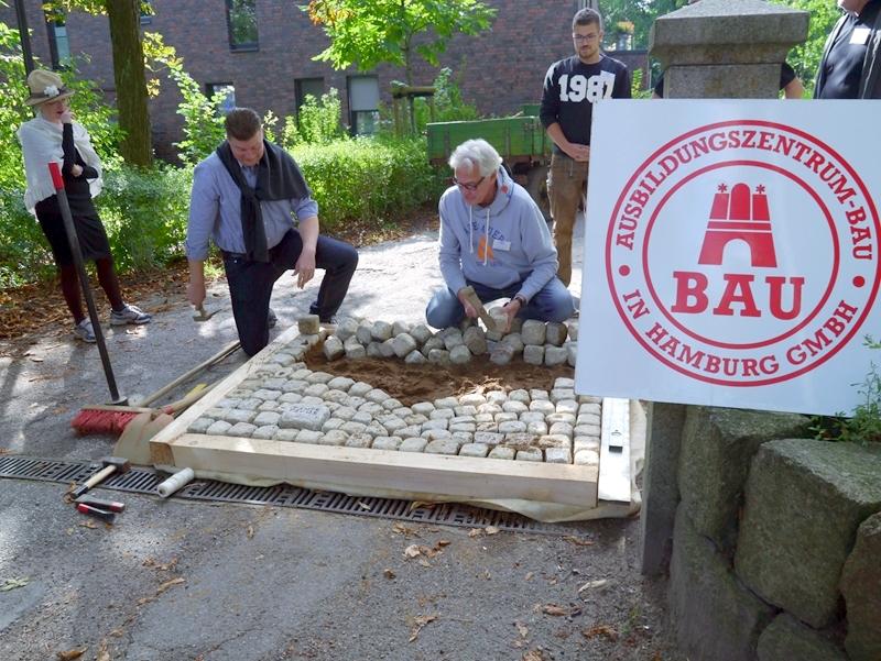SPD-Fraktionschef Dr. Andreas Dressel und Vorstandsvorsitzender Andreas Meyer klopfen symbolisch die ersten Pflastersteine zurecht.