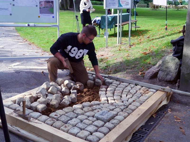 Leon Jahnke vom AZB zeigt, wie es mal aussehen soll: Viele Bögen in kleinen Steinen, insgesamt 13 Tonnen Kleinpflaster auf ca. 500 Quadratmeter.